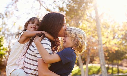 Alleinerziehende Mutter mit Kindern auf dem Arm